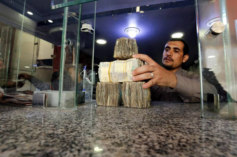 epa06990494 A Yemeni man holds Yemeni currency banknotes amid a continuous collapse of the Rial currency, at a currency exchange office in Sana'a, Yemen, 01 September 2018. According to reports, the Yemeni currency Rial has lost more than 100 percent in value against the US dollar where the exchange rate of the YR against one dollar amounted to about 600 YR compared to 250 YR at the beginning of the over three-year conflict in the Arab world's poorest country.  EPA/YAHYA ARHAB