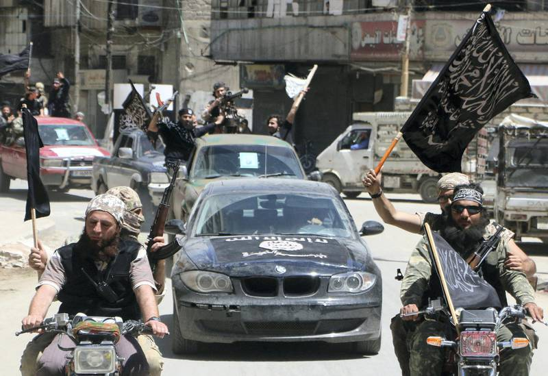 Fighters from Al-Qaeda's Syrian affiliate Al-Nusra Front drive in the northern Syrian city of Aleppo flying Islamist flags as they head to a frontline, on May 26, 2015. Once Syria's economic powerhouse, Aleppo has been divided between government control in the city's west and rebel control in the east since shortly after fighting there began in mid-2012. AFP PHOTO / AMC / FADI AL-HALABI (Photo by Fadi al-Halabi / AMC / AFP)