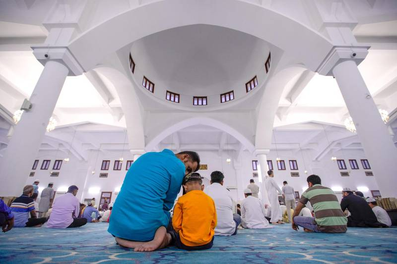 Abu Dhabi, United Arab Emirates, August 11, 2019.  Eid prayers at Zayed The 2nd Mosque. --  A father and son together for Eid prayers.Victor Besa/The NationalSection:  NAReporter: Haneen Dajani