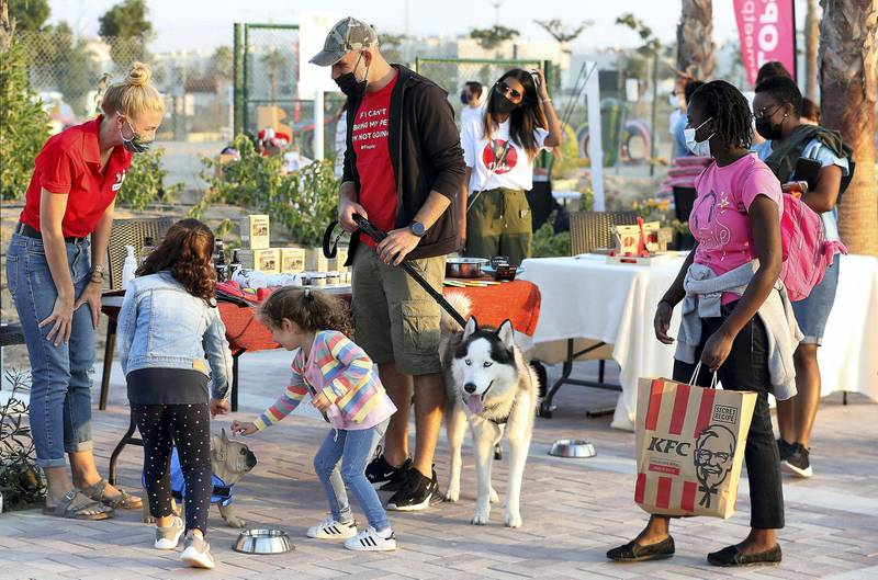 DUBAI, UNITED ARAB EMIRATES, December 10 – People with their dogs looking for items at the stalls during the official opening of  DAMAC Akoya Central Bark (dog park) in DAMAC Akoya Oxygen in Dubai. (Pawan Singh / The National) For Lifestyle/Online/Instagram. Story by Hayley