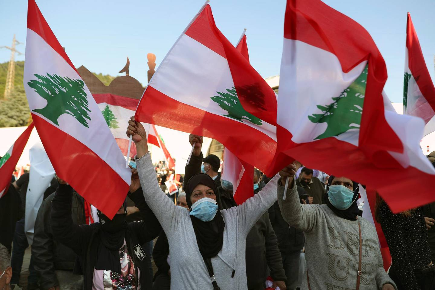 Muslims women wave Lebanese flags as Maronite Patriarch Bechara Rai speaks during a rally at the church's seat in Bkirki, northeast of Beirut, Lebanon, Saturday, Feb. 27, 2021. Thousands of people participated Saturday in a rally held in Bkerki, the headquarters of the Maronite Catholic church to express their support to Cardinal Bechara Rai's calls for Lebanon to become a neutral state and for an international conference to help Lebanon get out of its political and economic crisis. (AP Photo/Bilal Hussein)