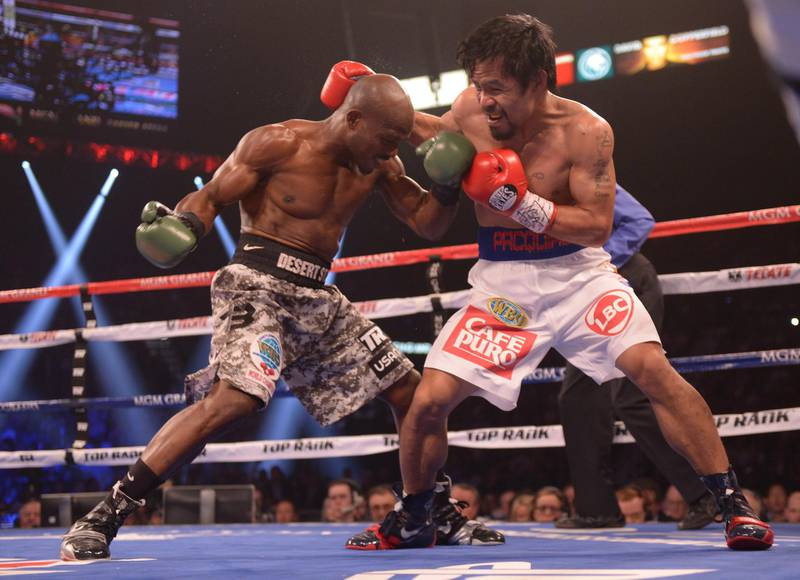 Timothy Bradley of the US (L) exchanges blows with Manny Pacquiao of Philippines (R) during their  WBO World Welterweight Championship title match at the MGM Grand Arena in Las Vegas, Nevada on April 12, 2014.    AFP PHOTO / JOE KLAMAR (Photo by JOE KLAMAR / AFP)