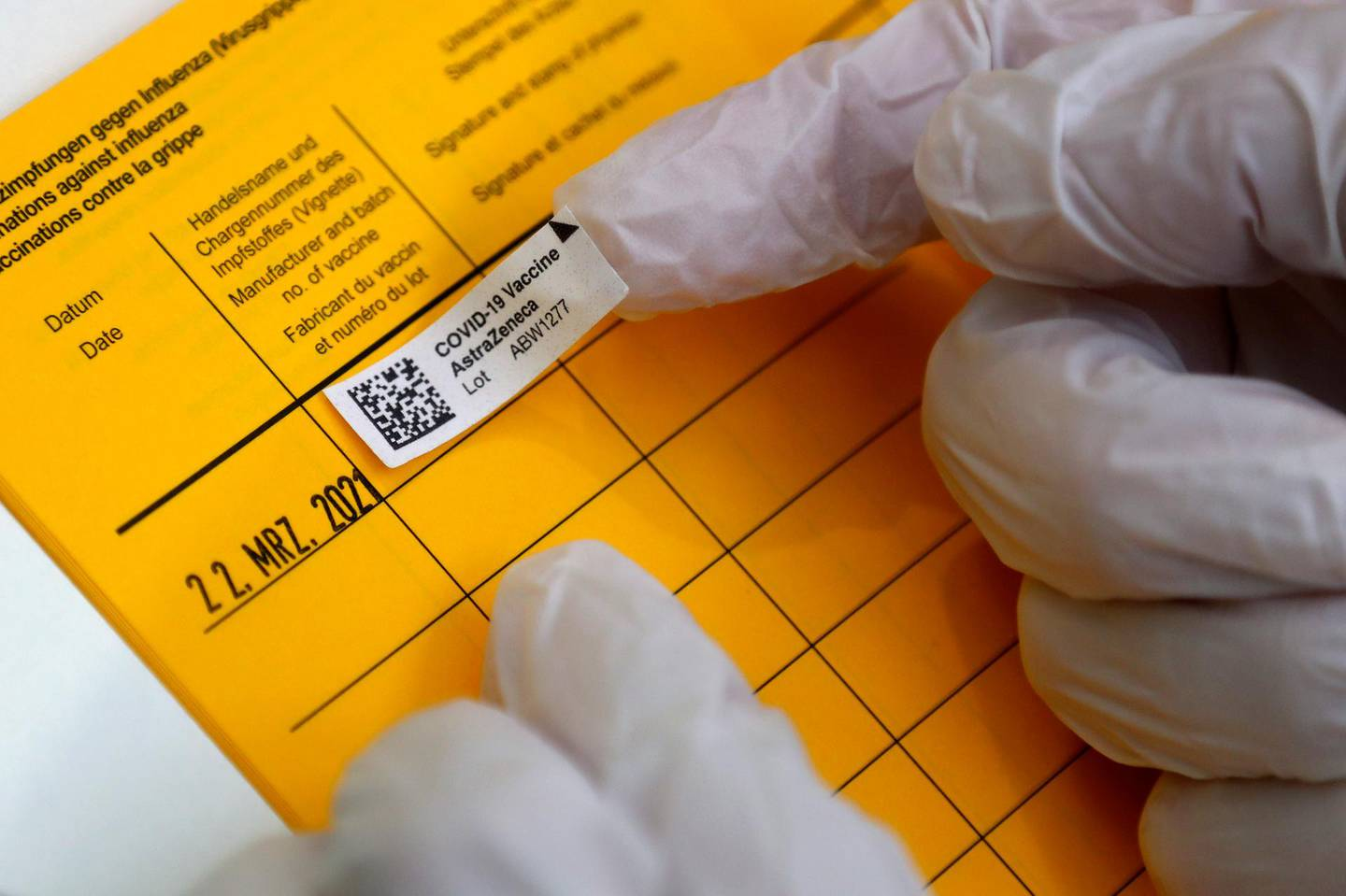 Medical staff fill in a vaccination pass at the local vaccination centre in Ebersberg near Munich, Germany, Monday, March 22, 2021. (AP Photo/Matthias Schrader)