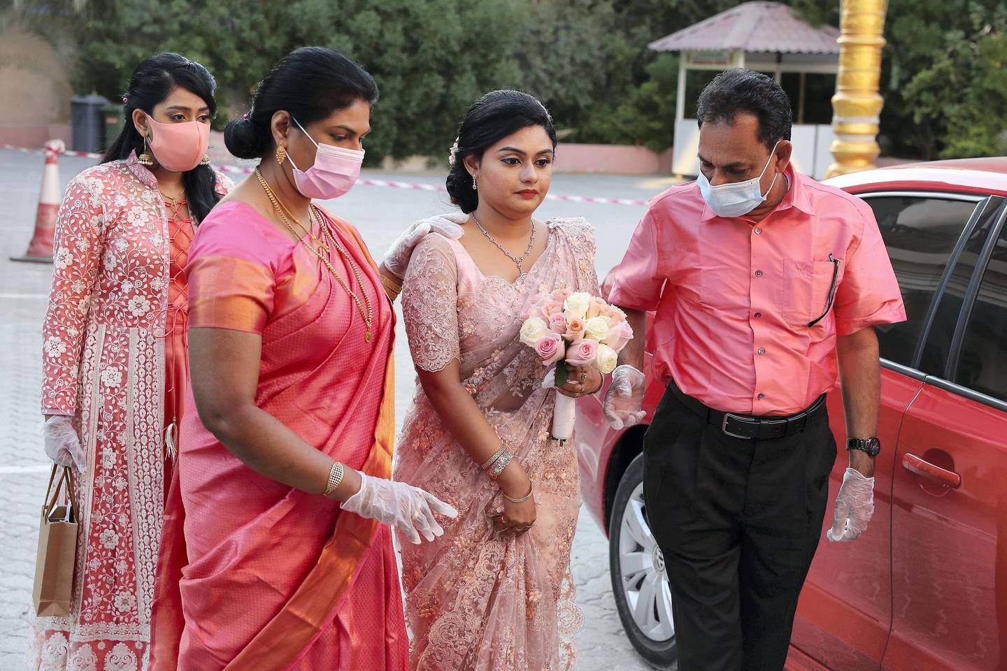DUBAI, UNITED ARAB EMIRATES , October 26– 2020 :- Jubee Vargheese (bride) with her parents coming for the marriage ceremony held at the St. Thomas Orthodox Cathedral in Dubai. Relatives and friends were wearing protective face mask and gloves as a preventive measure against the spread of coronavirus and maintaining social distance during the ceremony.  (Pawan Singh / The National) For News/Online/Instagram. Story by Kelly