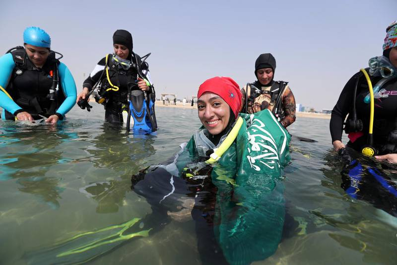 Abrar Abu Abdullah, a Saudi female diver smiles as she wears Saudi national flag over her shoulders as she enters the sea to dive at Half Moon Beach open-water dive site in Dhahran, Saudi Arabia, September 15, 2018. Picture taken September 15, 2018. REUTERS/Hamad I Mohammed
