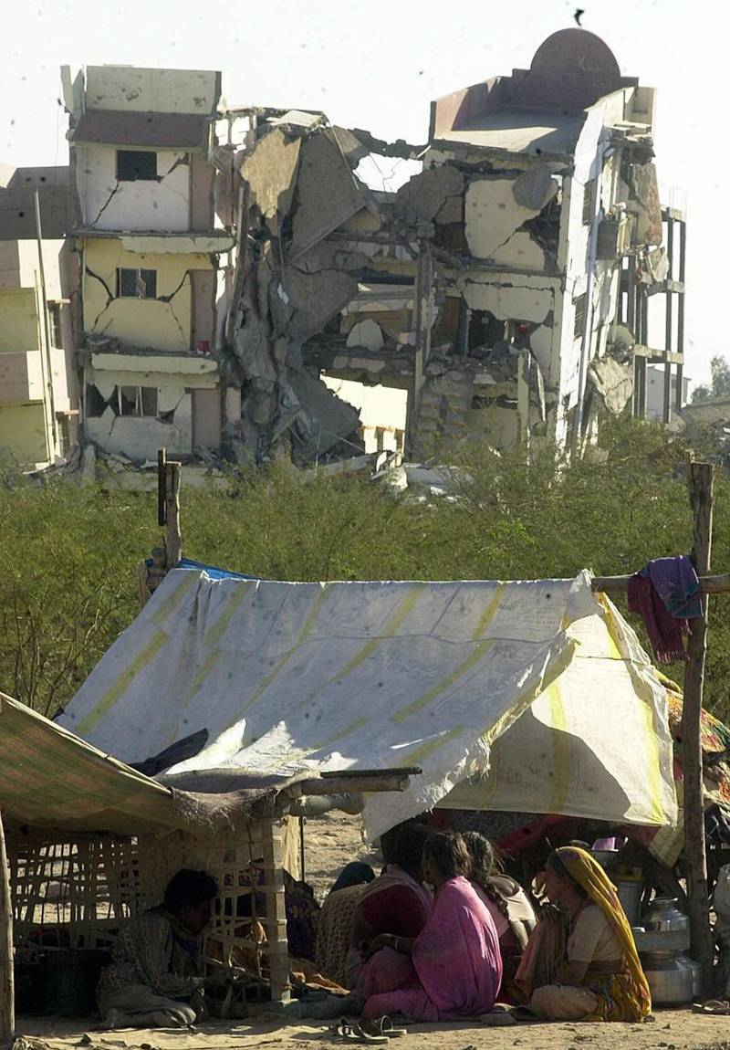 A homeless family takes temporary shelter in a make-shift tent, 27 January 2001, in front of a wrecked building in Bhuj town in Gujarat that was destroyed in an earthquake that struck north western India 26 January rendering thousands homeless. At least 3000 people are feared dead as a result of the tremor, with casualties expected to rise. AFP PHOTO/Arko DATTA (Photo by ARKO DATTA / AFP)