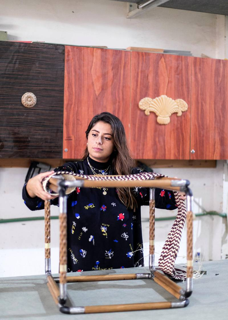 SHARJAH, UNITED ARAB EMIRATES. 7 SEPTEMBER 2019. Lana El Samman test a khoos sample on a prototype of her table, which is being produced in Aden Furniture & Wood factory.Lana El Samman is currently a resident designer in Tashkeel's Tanween program. The program is open to emerging designers, makers and artisans living and working in the UAE.Lana El Samman is of Lebanese origin, and grew up in Beirut and later Canada, where she studied interior design followed by a Master's degree at the Florence Institute of Design, Italy. Her career began as a teaching assistant at the American University of Sharjah before joining Sharjah Art Foundation, which has been her home for the past eight years working as an interior designer and then progressing to become a significant member of the production programme. In the SAF Production Programme, Samman has had the chance to further her furniture design practice and create pieces used by the Foundation for various events.(Photo: Reem Mohammed/The National)Reporter: KATE HAZELLSection: WK