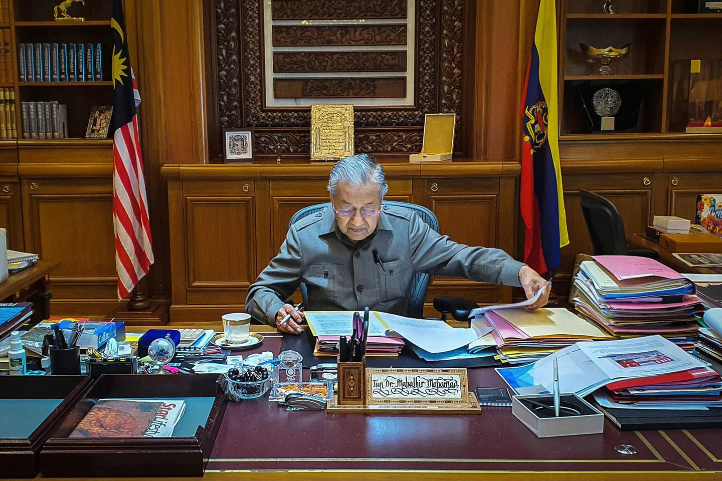In this photo released by Prime Minister Office, Malaysian Prime Minister Mahathir Mohamad works at his office in Putrajaya, Malaysia, Tuesday, Feb. 25, 2020. Malaysia's king accepted Mahathir's shocking resignation Monday. The move came in tandem with plans by Mahathir's supporters to team up with opposition parties to form a new government and foil the transition of power to his named successor, Anwar Ibrahim. (Prime Minister Office via AP)