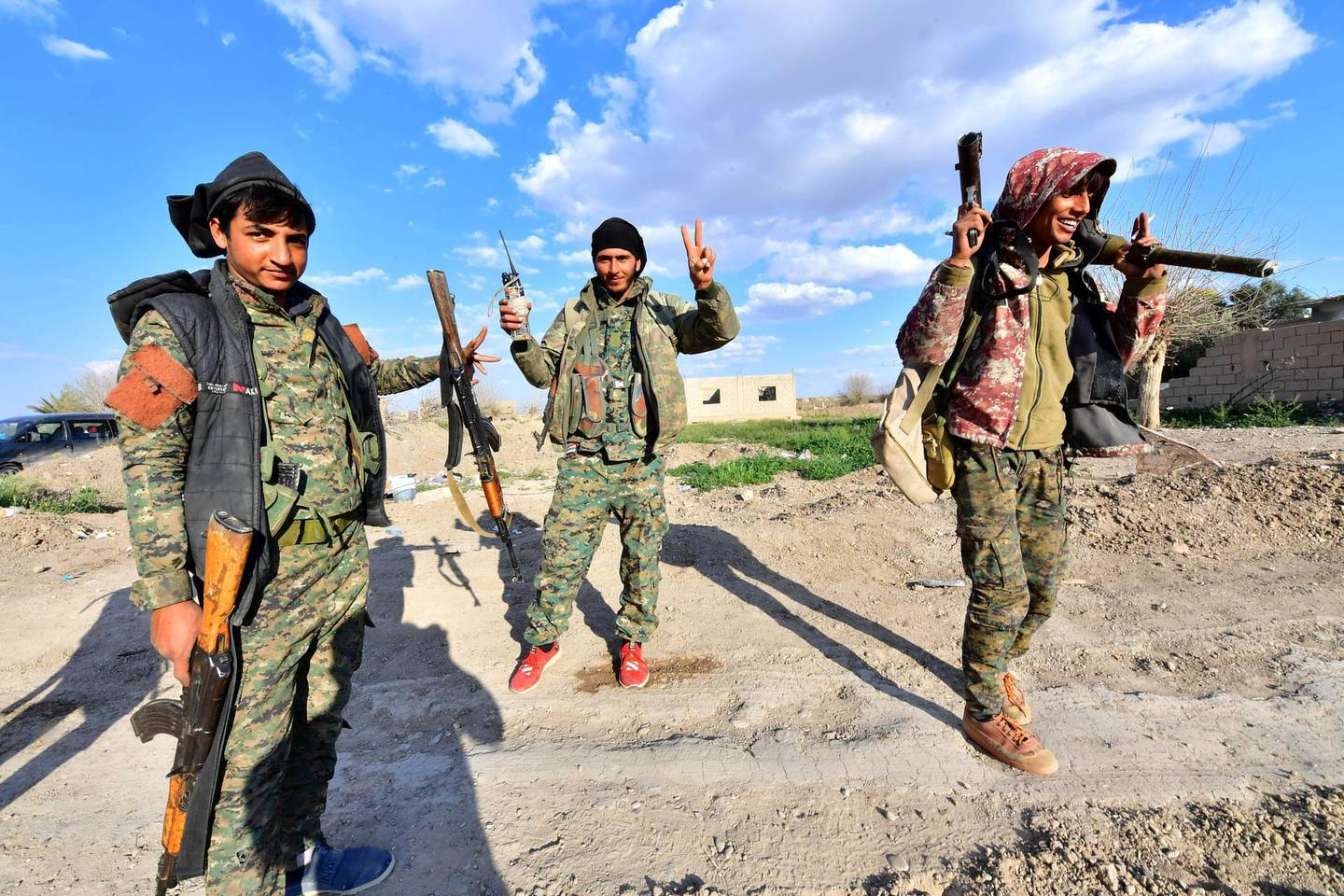 """Fighters from the Syrian Democratic Forces (SDF) gesture the """"V"""" for victory sign as they come back from the frontline in the Islamic State group's last remaining position in the village of Baghouz in the countryside of the eastern Syrian province of Deir Ezzor on March 19, 2019. - The Kurdish-led SDF have been closing in on IS fighters holed up in a small sliver of territory in the village of Baghouz in eastern Syria since January. (Photo by GIUSEPPE CACACE / AFP)"""