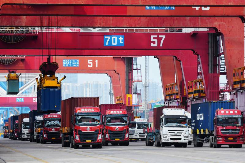 In this June 2, 2020, photo, trucks line up to transport containers at the container port in Qingdao in eastern China's Shandong province. China's exports and imports both fell in May as the coronavirus and trade tensions with the U.S. weighed on demand both at home and abroad. (Chinatopix via AP)
