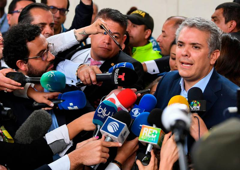 Colombian presidential candidate Ivan Duque, for the Democratic Centre party, speaks to the press at a polling station in Bogota during the first round of the presidential election in Colombia on May 27, 2018. Voters went to the polls Sunday to choose a new president of Colombia in a divisive election that is likely to weigh heavily on the future of the government's fragile peace deal with the former rebel movement FARC. / AFP / Luis ACOSTA