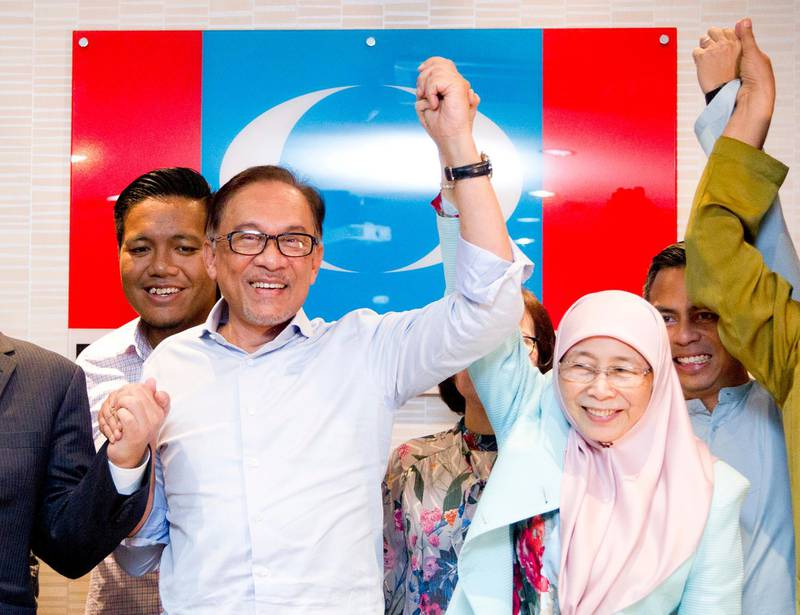 Malaysia's prime minister-in-waiting Anwar Ibrahim, left, poses with his wife Deputy Prime Minister Wan Azizah Wan Ismail after a press conference at the People's Justice Party headquarters in Petaling Jaya, Malaysia, Friday, Sept. 21, 2018. Anwar said that he has no reason to doubt his former political nemesis will hand over the leadership position within two years as planned after sorting out deep-seated issues like corruption. (AP Photo/Yam G-Jun)