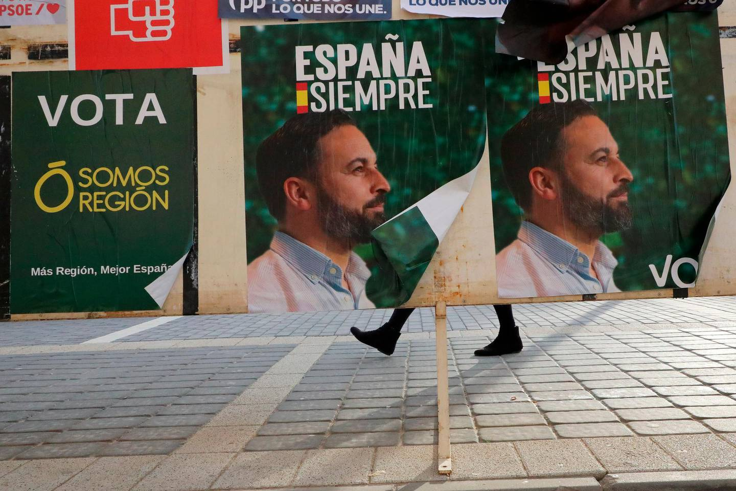 A woman walks past banners of Spain's far-right Vox party candidate Santiago Abascal in Torre-Pacheco, Spain, Monday, Nov. 11, 2019. The farming town of Torre-Pacheco, heavily reliant on foreign workers, voted in droves for Vox, which has vowed to build walls to contain migrants and prioritize the needs of Spaniards. (AP Photo/Sergio Rodrigo)