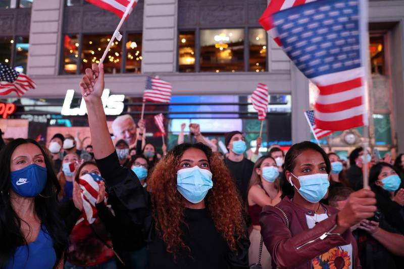 People react as they watch a speech by Democratic U.S. presidential nominee Joe Biden in Times Square after news media announced he has won the 2020 U.S. presidential election in Manhattan, New York, U.S., November 7, 2020. Picture taken November 7, 2020. REUTERS/Caitlin Ochs
