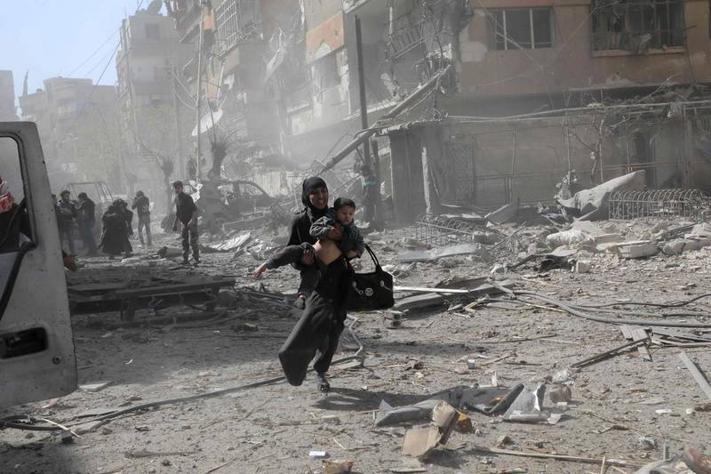 TOPSHOT - A Syrian woman holds a child and runs for cover following Syrian government air strikes on the Eastern Ghouta rebel-held enclave of Douma, on the outskirts of the capital Damascus on March 20, 2018. Syrian regime and allied forces battled to suppress the last pockets of resistance in and around Damascus while the beleaguered Kurds in the north braced for further Turkish advances. Assad has in recent months brought swathes of territory back under his control thanks to heavy Russian involvement, as well as support from other forces such as the Iran-backed Lebanese Hezbollah militia. Eastern Ghouta's main town of Douma remains under rebel control but even as a trickle of emergency medical evacuations was scheduled to continue, the regime continued to pound the enclave. / AFP PHOTO / HAMZA AL-AJWEH