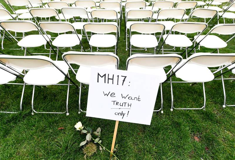 FILE PHOTO: A protest sign stands in front of a row of chairs as family members of victims of the MH17 crash lined up empty chairs for each seat on the plane during a protest outside the Russian Embassy in The Hague, Netherlands March 8, 2020.  REUTERS/Piroschka van de Wouw/File Photo