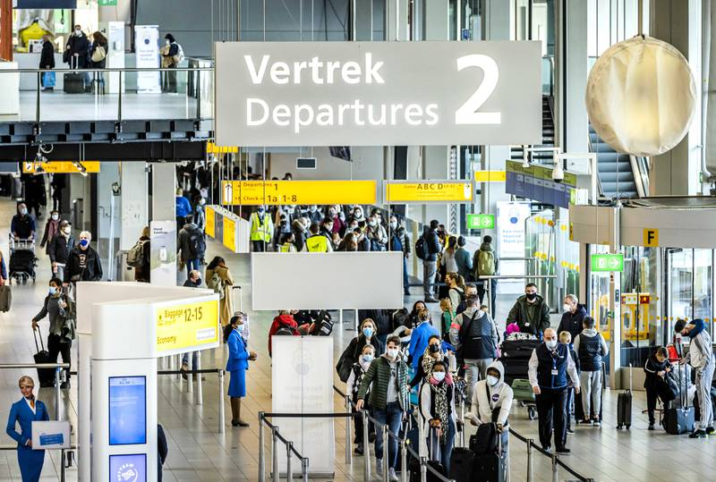 epa08889854 Travellers in the departure hall of Schiphol Amsterdam Airport, in Amsterdam, the Netherlands, 17 December 2020. Tour operators including TUI and Corendon are canceling their air travel to holiday destinations due to increased numbers of people infected with coronavirus Covid-19 in most countries. Schiphol also advises people not to fly if they don't really have to.  EPA/REMKO DE WAAL