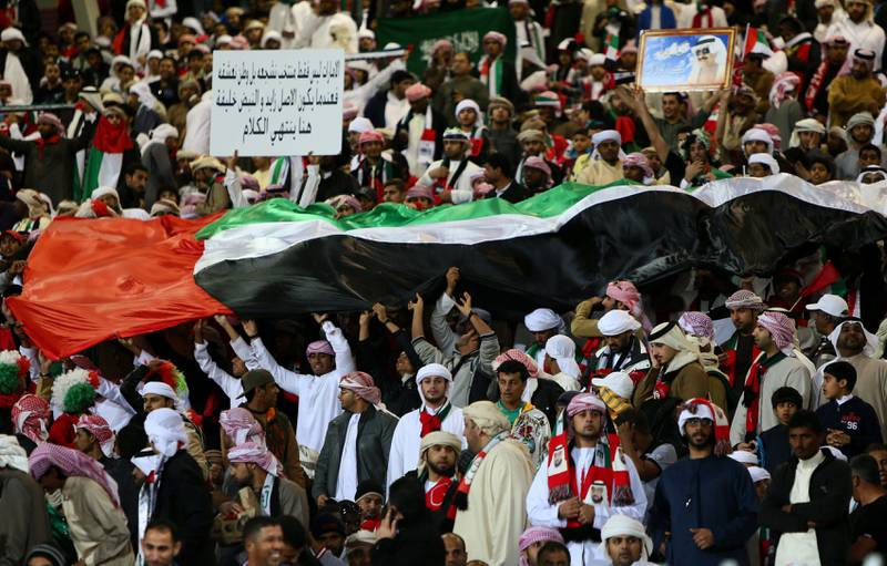 Supporters of the United Arab Emirates (UAE)' national football team wave a giant flag prior the start of the Gulf Cup's final football match between UAE and Iraq on January 18, 2013 in Manama . AFP PHOTO/MARWAN NAAMANI  *** Local Caption ***  288813-01-08.jpg