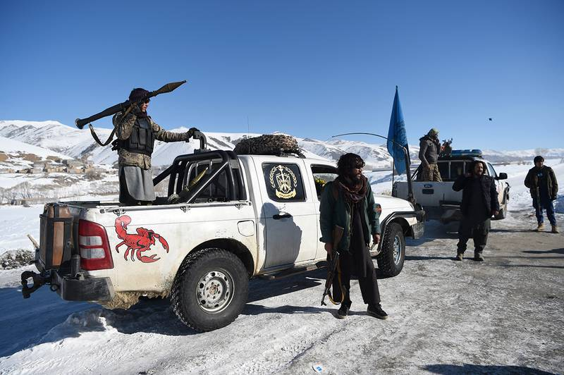 In this photo taken on January 9, 2021, Hazara armed militia for the Resistance for Justice Movement, keep watch along a road covered in snow in front of their base during a patrol against Taliban insurgents at Hisa-e-Awali Behsud district of Maidan Wardak Province. - Comprising roughly 10 to 20 percent of Afghanistan's 38-million population, Hazaras have long been persecuted for their largely Shiite faith by Sunni hardliners in a country wracked by deep ethnic divisions. (Photo by WAKIL KOHSAR / AFP) / TO GO WITH'Afghanistan-Hazara-violence', by David STOUT, Najiba NOORI