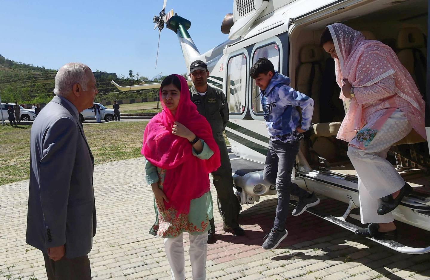 Pakistani activist and Nobel Peace Prize laureate Malala Yousafzai (C), meets with the principal (2L) of all-boys Swat Cadet College Guli Bagh, upon her arrival during her hometown visit, some 15 kilometres outside of Mingora, on March 31, 2018. Malala Yousafzai landed in the Swat valley on March 31 for her first visit back to the once militant-infested Pakistani region where she was shot in the head by the Taliban more than five years ago. / AFP PHOTO / ABDUL MAJEED