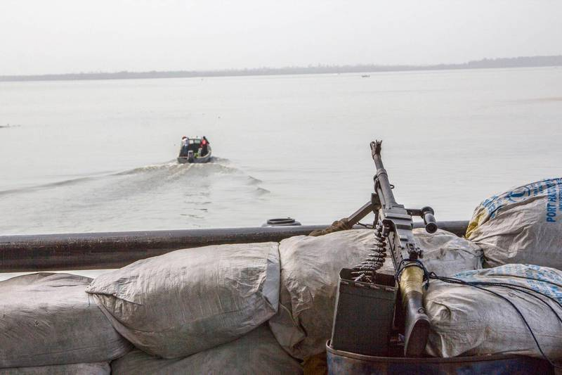A machine gun is seen on a sandbag on a boat off the Atlantic coast in Nigeria's Bayelsa state December 19, 2013. Nigeria's navy has installed eight automated, camera-equipped surveillance towers in the waters just off its coast, in an effort to tackle a surge in pirate attacks and crude oil theft that have blighted Africa's top energy producer this year. Pirate attacks off Nigeria have jumped by a third this year as ships passing through West Africa's Gulf of Guinea, a major commodities route, have come under threat from gangs seeking to snatch cargoes or hold crews for ransom. Picture taken December 19, 2013. REUTERS/Stringer (NIGERIA - Tags: MILITARY POLITICS MARITIME)