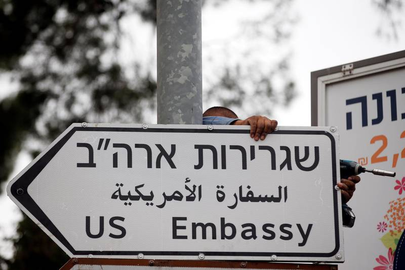 FILE PHOTO: A worker hangs a road sign directing to the U.S. embassy, in the area of the U.S. consulate in Jerusalem, May 7, 2018. REUTERS/Ronen Zvulun/File Photo