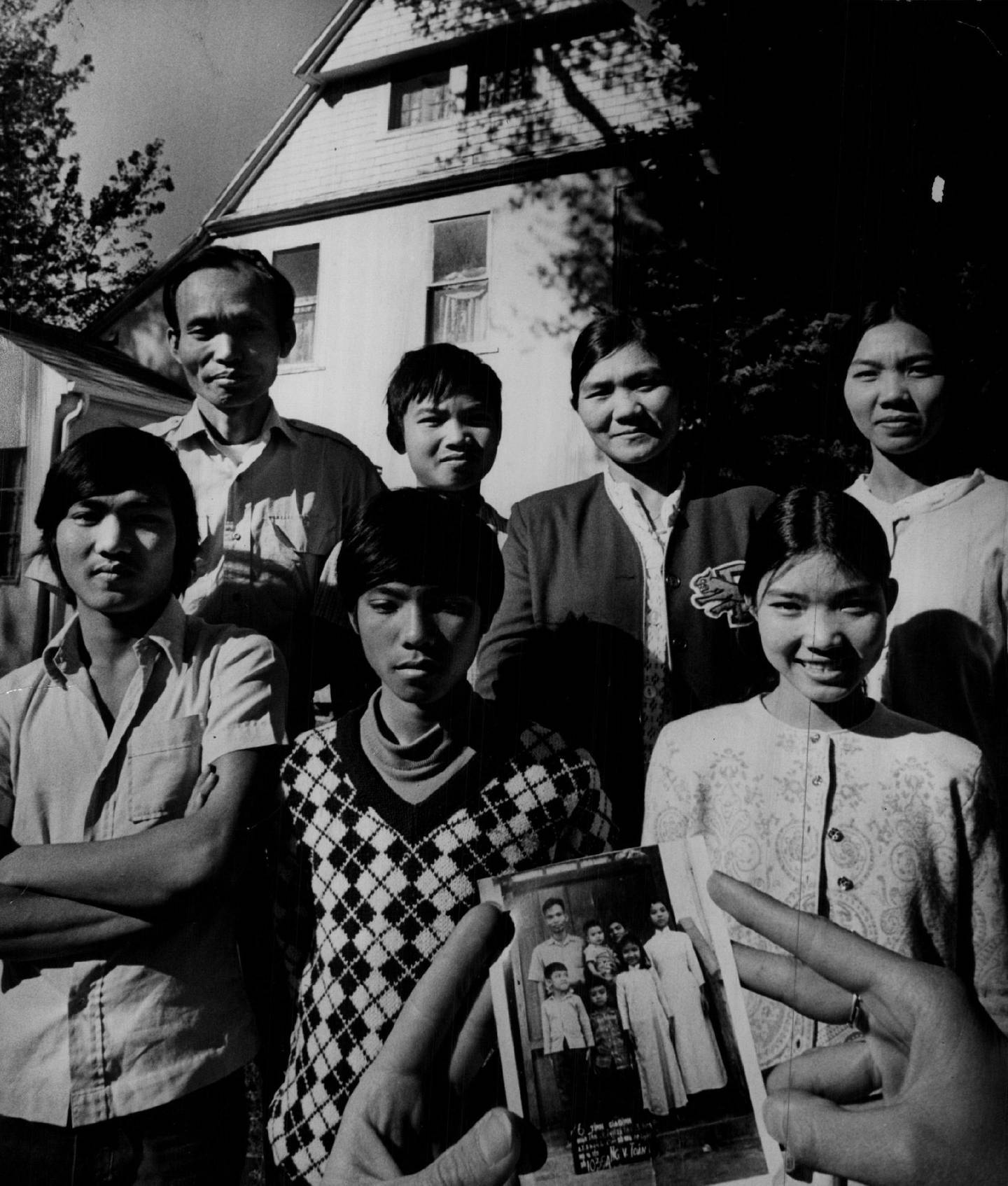 OCT 29 1975, NOV 2 1975; Vietnamese Family Has Come A Long Way; Members of the Nguyen Van Toan family, which arrived in Denver a week ago, pose behind photo taken of the same group about 10 years ago. In the back row, from the left, in both photos are Toan; Ton; Toan's wife, Thoa Thi Trang, and Sang. Front row, from the left, ate Tuyen, Tung, and Son. The Nguyen family sailed 1,400 miles across the South China Sea from Vietnam to Manila last spring to flee from South Vietnam. (Story, Photos On Page 29); Vietnam - (Refugees);  (Photo By Steve Larson/The Denver Post via Getty Images)