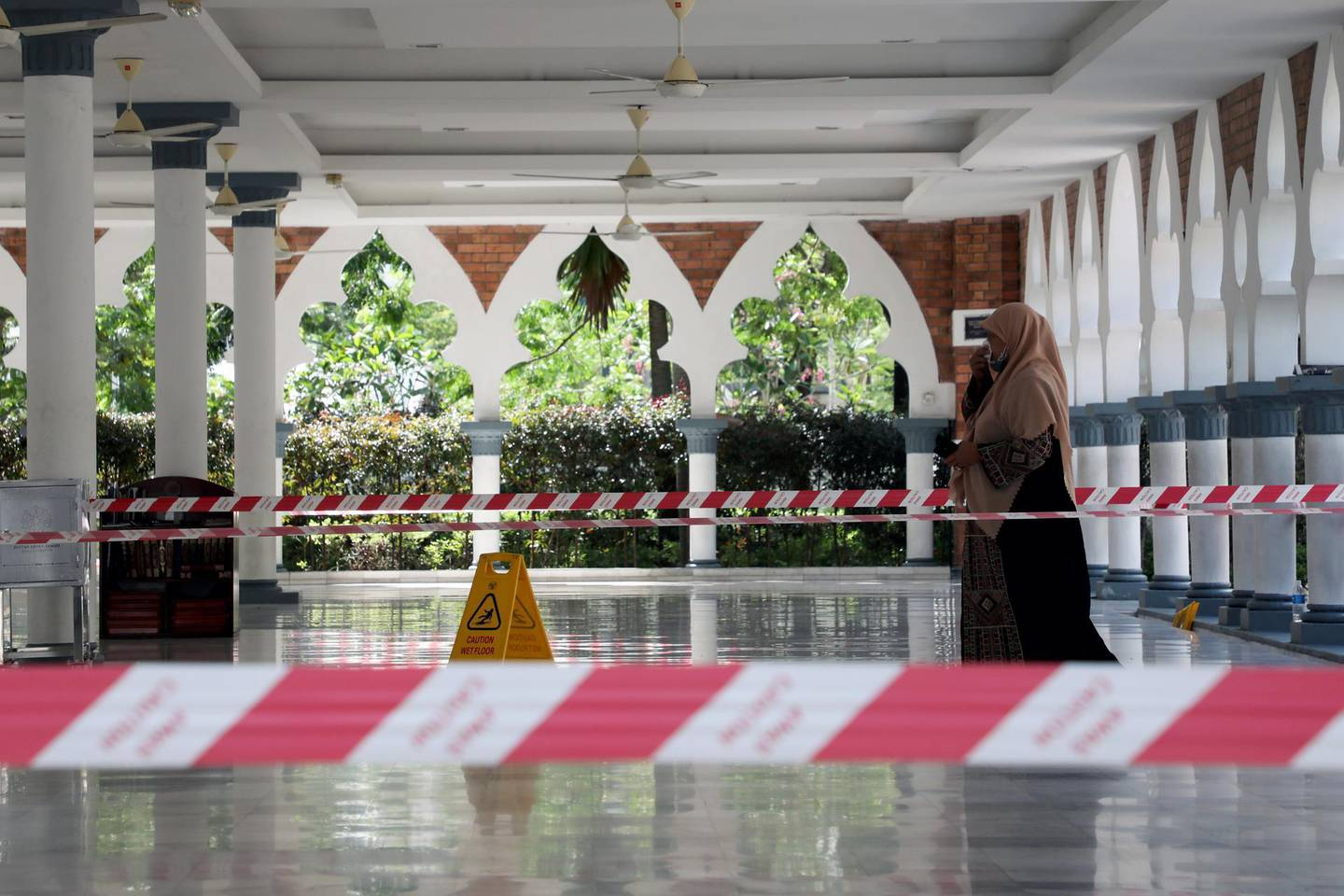 A woman wearing a protective mask walks at a mosque following the outbreak of coronavirus, in Kuala Lumpur, Malaysia March 16, 2020. REUTERS/Lim Huey Teng