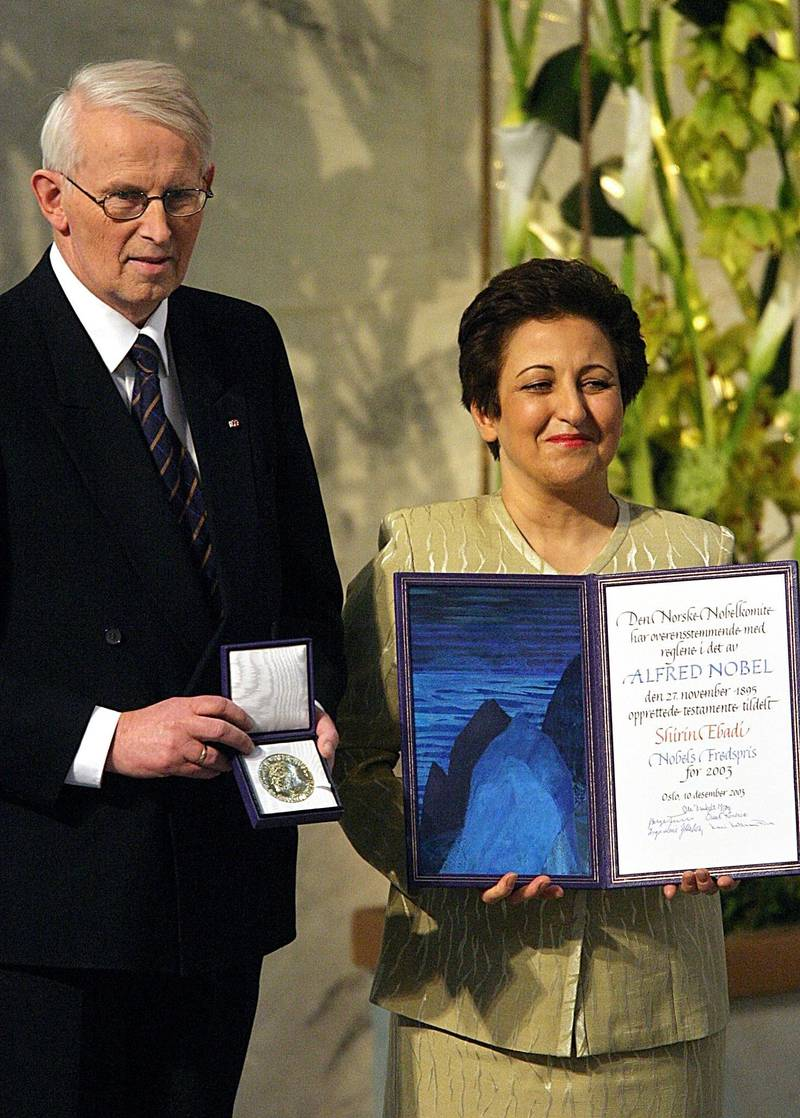 Iranian lawyer and human rights activist Shirin Ebadi (R) and Nobel Committee chairman Ole Danbolt Mjoes (L) poses with the medal and diploma after Ebadi was awarded the 2003 Nobel prize during a ceremony in Oslo's city hall 10 December 2003. Ebadi, 56, received the Nobel Peace Prize at a ceremony in Oslo on Wednesday for her democracy-building efforts and her work to improve human rights in Iran, making her the first Muslim woman to receive the award.AFP PHOTO / ODD ANDERSEN (Photo by ODD ANDERSEN / AFP)