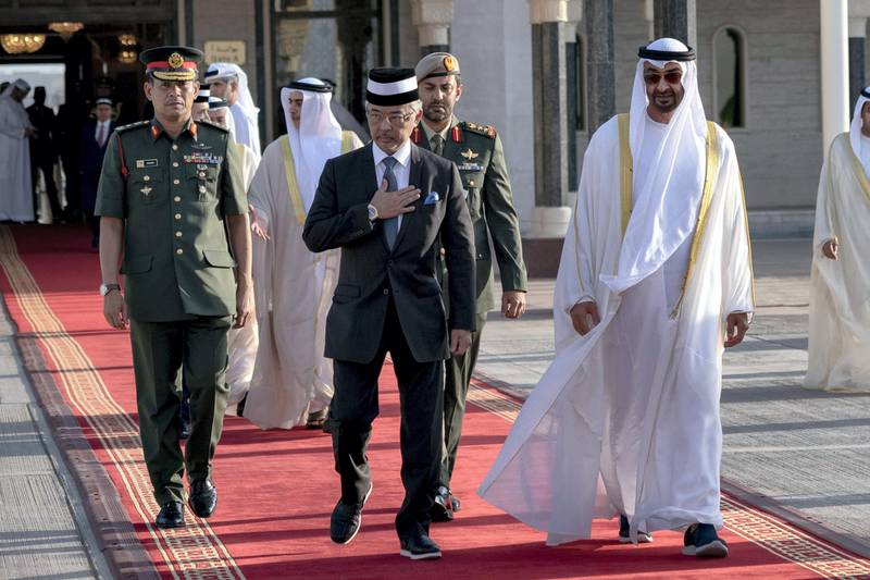 ABU DHABI, UNITED ARAB EMIRATES - June 14, 2019: HH Sheikh Mohamed bin Zayed Al Nahyan, Crown Prince of Abu Dhabi and Deputy Supreme Commander of the UAE Armed Forces (R) bids farewell to HM King Sultan Abdullah Sultan Ahmad Shah of Malaysia (2nd R), at the Presidential Airport.  ( Hamad Al Kaabi / Ministry of Presidential Affairs ) ---
