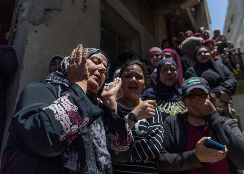 Palestinian women cry while taking a last look at the body of Mohammad Daraghmeh at the family house during his funeral in the West Bank village of Lubban, near Nablus, Wednesday, May 12, 2021. Israeli soldiers opened fire yesterday at a Palestinian vehicle at an army checkpoint north of the West Bank, killing Daraghmeh, a passenger, and critically wounding another, the Palestinian health ministry said. (AP Photo/Nasser Nasser)