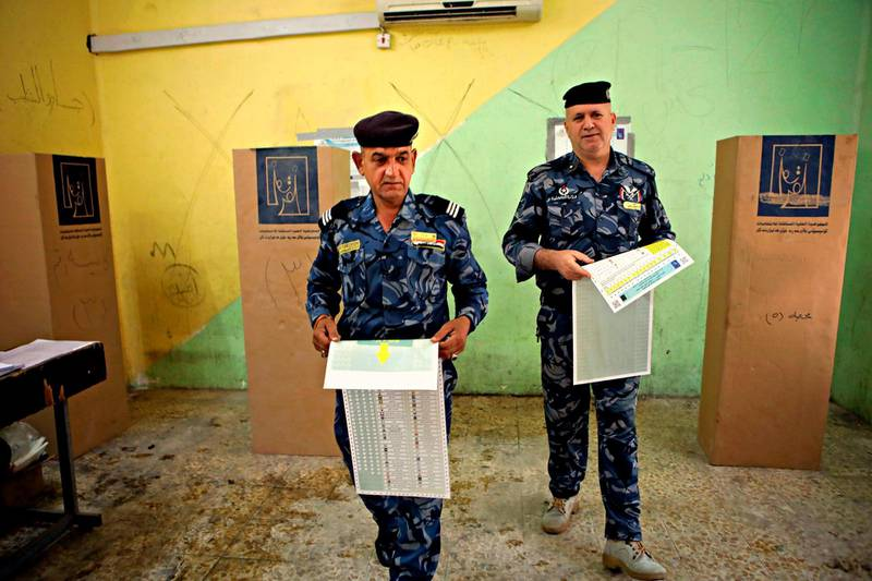 Federal policemen prepare to cast their votes at a polling station in Basra, 340 miles (550 kilometers) southeast of Baghdad, Iraq, Thursday, May 10, 2018. Soldiers and security forces cast ballots in early voting ahead of Saturday's parliamentary elections. (AP Photo/Nabil al-Jurani)
