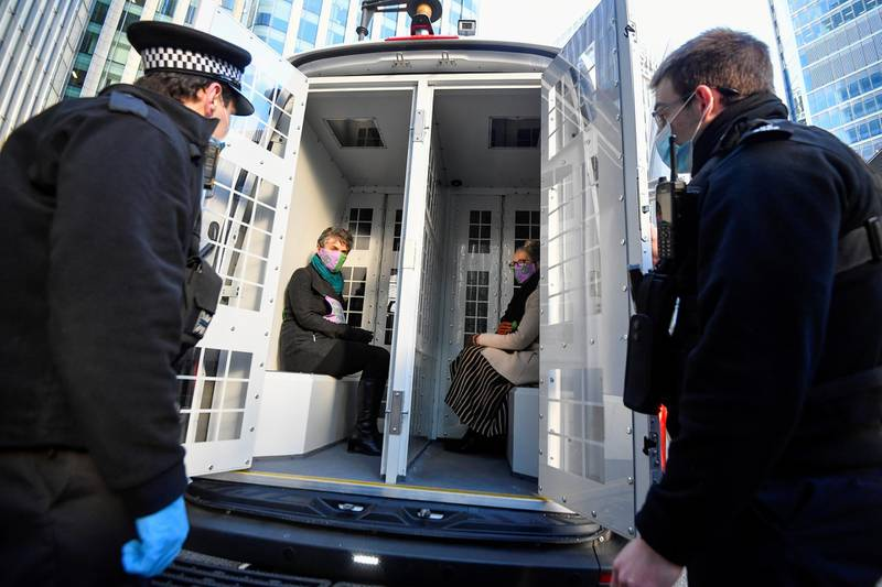 Activists from the Extinction Rebellion, a global environmental movement, sit inside a police car after being detained outside the Barclays offices, in Canary Wharf, London, Britain, April 7, 2021. REUTERS/Toby Melville