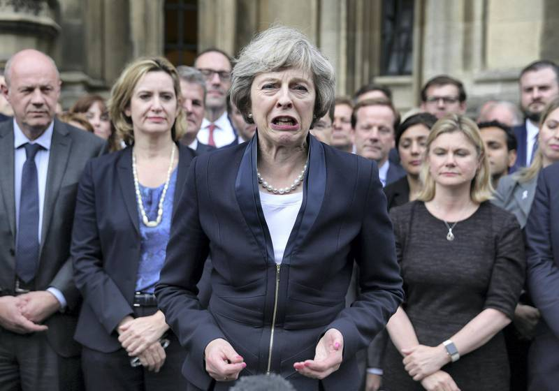 Britain's new Conservative Party leader Theresa May (C) speaks to members of the media at The St Stephen's entrance to the Palace of Westminster in London on July 11, 2016. - Theresa May will on Wednesday become the prime minister who leads Britain's into Brexit talks after her only rival in the race to succeed David Cameron pulled out unexpectedly. May was left as the only contender standing after the withdrawal from the leadership race of Andrea Leadsom, who faced criticism for suggesting she was more qualified to be premier because she had children. (Photo by DANIEL LEAL-OLIVAS / AFP)