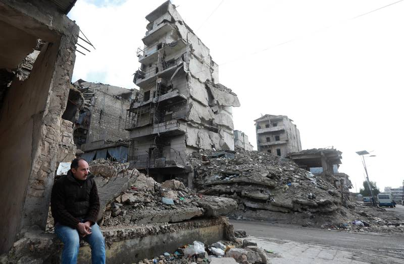 A man sits on the rubble of a building that was destroyed during battles between rebel fighters and regime forces, in the former opposition held district of Salaheddin in the northern Syrian city of Aleppo on February 11, 2019.  three years after the Syrian regime regained, with Russian firepower help, rebel-held territory and took full control of the country's second city. / AFP / LOUAI BESHARA