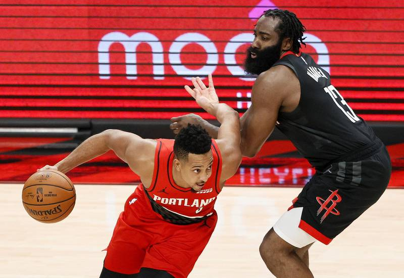 PORTLAND, OREGON - DECEMBER 26: CJ McCollum #3 of the Portland Trail Blazers dribbles past James Harden #13 of the Houston Rockets during overtime at Moda Center on December 26, 2020 in Portland, Oregon. NOTE TO USER: User expressly acknowledges and agrees that, by downloading and/or using this photograph, user is consenting to the terms and conditions of the Getty Images License Agreement.   Steph Chambers/Getty Images/AFP == FOR NEWSPAPERS, INTERNET, TELCOS & TELEVISION USE ONLY ==