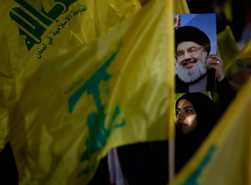 A Hezbollah supporter holds up a portrait of Hezbollah leader Sayyed Hassan Nasrallah, during a rally marking the 12th anniversary of the 2006 Israel-Hezbollah war, in Beirut, Lebanon, Tuesday, Aug. 14, 2018. The leader of Lebanon's militant Hezbollah group says U.S. sanctions against Iran and his group will not have major effects on them. (AP Photo/Hussein Malla)