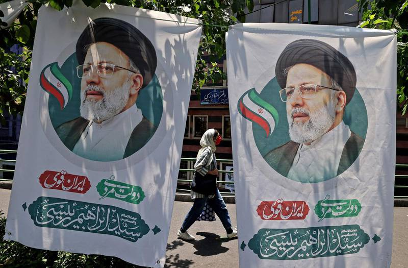 An Iranian woman walks past banners of ultraconservative cleric and presidential candidate Ebrahim Raisi, in Tehran, on June 17, 2021, on the eve of the Islamic republic's presidential election.  / AFP / ATTA KENARE