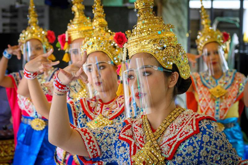 TOPSHOT - Traditional Thai dancers wearing protective face shields perform at the Erawan Shrine, which was reopened after the Thai government relaxed measures to combat the spread of the COVID-19 novel coronavirus, in Bangkok on May 4, 2020. Thailand began easing restrictions related to the COVID-19 novel coronavirus on May 3 by allowing various businesses to reopen, but warned that the stricter measures would be re-imposed should cases increase again. / AFP / Mladen ANTONOV