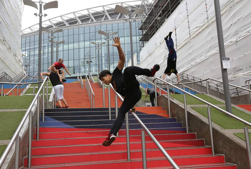 """FILE - In this Aug. 16, 2018, file photo, participants of the Parkour Generations work on their practice runs outside of Wembley Stadium ahead of the 13th Rendezvous International Parkour Gathering in London. Global organizers of parkour are urging the IOC not to add the street-running sport to the 2024 Paris Olympics at a meeting next week. The Parkour Earth group has for years opposed what it calls a """"hostile takeover"""" of the sport by the Olympic-recognized International Gymnastics Federation. Parkour Earth said Tuesday, Dec. 1, 2020 in an open letter to the International Olympic Committee that the world gymnastic body's """"encroachment and misappropriation of our sport continues."""" (AP Photo/Nishat Ahmed, File)"""