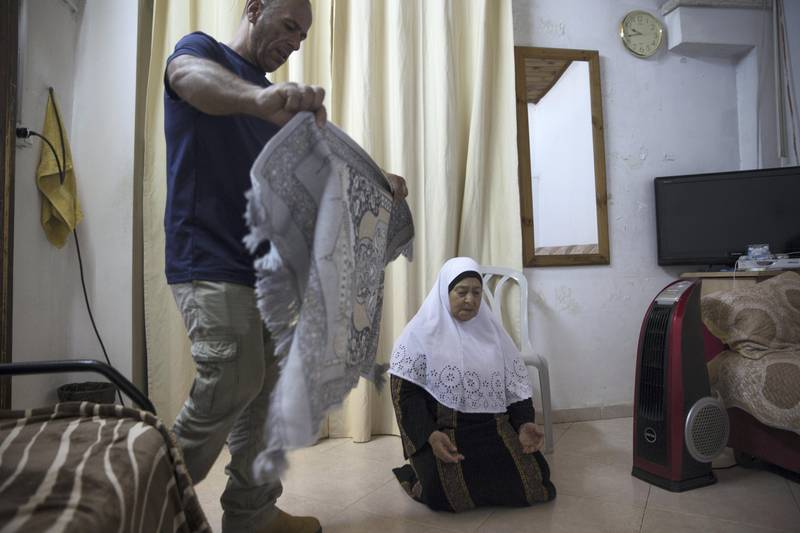 Mohamed Shamasneh prepares the prayer carpet for his mother Fahima as she prays in the salon of the family's tiny basement  home in the East Jerusalem neighborhood of Sheik Jarrah on August 11,2017.  When the Shamasne family first moved into their home  in the 1960s, East Jerusalem was controlled by Jordan and their monthly rent was paid to  Jordanian authorities but since  Israel annexed East Jerusalem in 1967, the Shamasne family has paid their rent to Israel's general custodian in order to remain in the building. The family claims that their payments were suddenly rejected in 2009 , and they were informed that the property had been claimed by Israeli Jews whose ancestors had lived there decades previously.Although the family has spent years fighting to remain in the home , the Israeli high court has ruled that the family must evacuate the home before August 9. Mohamed  says that the Israeli authorities will have to remove the family by force .(Photo by Heidi Levine for The National).