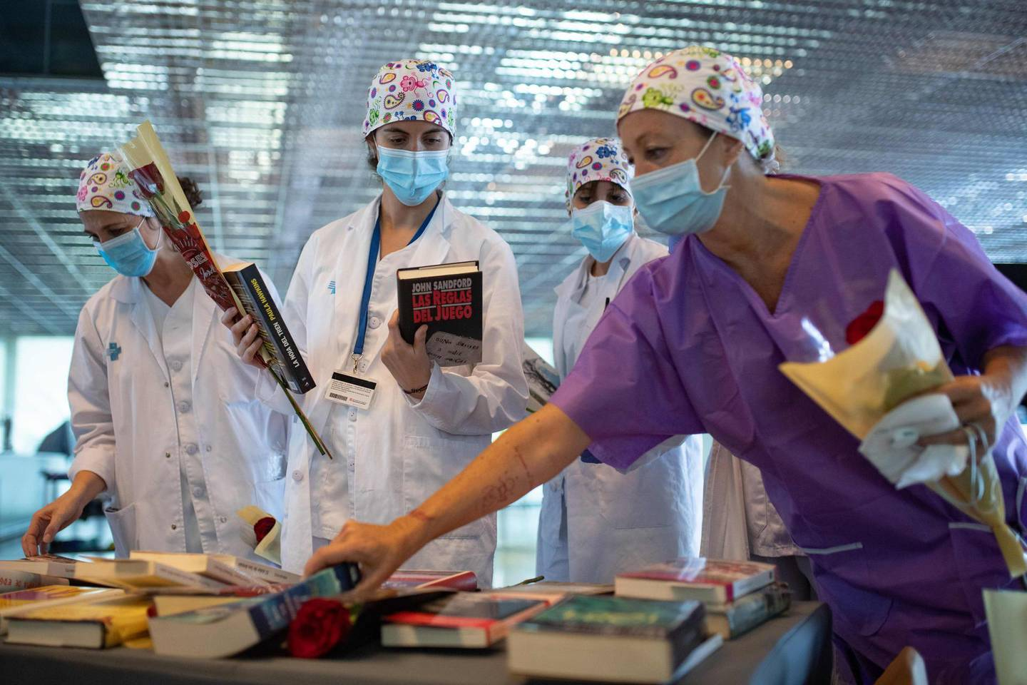 """Healthcare workers holding roses pick up books donated to the field hospital of Hotel Catalonia Fira in Barcelona on April 23, 2020 during the Sant Jordi festivities marking Saint George's day. Traditionally men give women roses and women give men a book to celebrate the Catalan holiday also know as """"The Day of the Rose"""" or """"The Day of the Book"""". Spain said 440 people died in the past 24 hours from the new coronavirus, a slight increase for the third day running, bringing the overall death toll to 22,157. / AFP / Josep LAGO"""