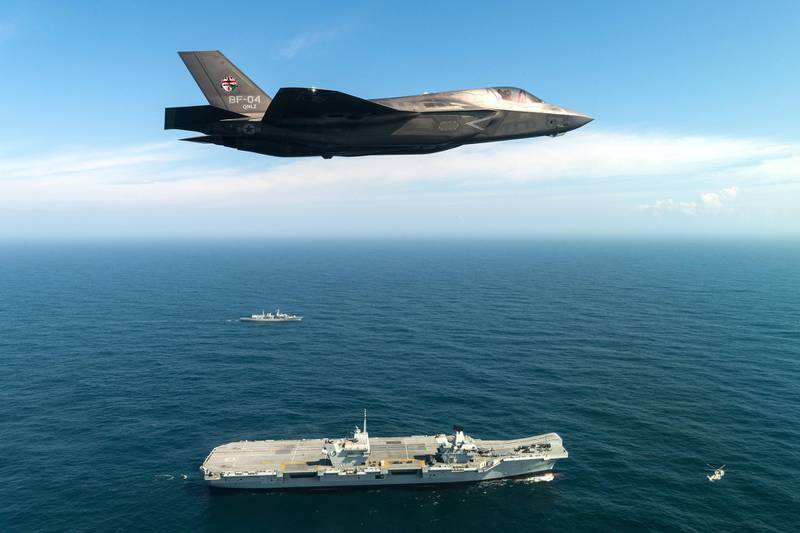PORTSMOUTH, ENGLAND - SEPTEMBER 26: In this handout image provided by the Ministry of Defence, An F-35B fighter jet flies over HMS Queen Elizabeth on September 26, 2018 in Portsmouth, England.  Two F-35B Lightning II fighter jets have successfully landed onboard HMS Queen Elizabeth for the first time, laying the foundations for the next 50 years of fixed wing aviation in support of the UKs Carrier Strike Capability. Royal Navy Commander, Nathan Gray, 41, made history by being the first to land on, carefully manoeuvring his stealth jet onto the thermal coated deck. He was followed by Squadron Leader Andy Edgell, RAF, both of whom are test pilots, operating with the Integrated Test Force (ITF) based at Naval Air Station Patuxent River, Maryland. Shortly afterwards, once a deck inspection has been conducted and the all-clear given, Cdr Gray became the first pilot to take off using the ships ski-ramp. (Photo by Lockheed Martin/Ministry of Defence via Getty Images)