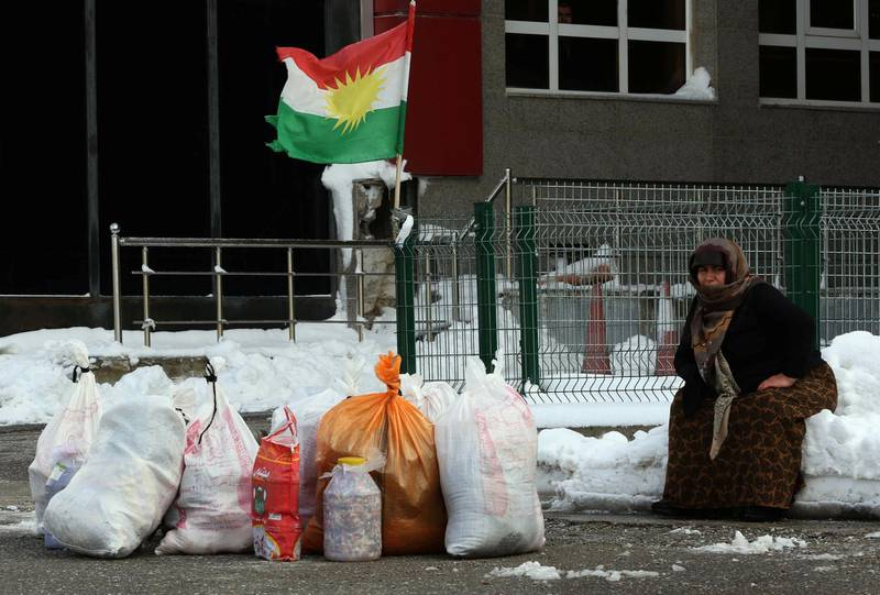 A woman sits on the snow with Kurdish flags in the background at the Iran-Iraq border crossing of Haji Omran on January 3, 2018, one day after two border posts were reopened between Iraqi Kurdistan and the Islamic republic. - The borders had been closed in response to an independence vote rejected by Baghdad and neighbouring countries last year. The Iranian consulate in the Kurdish autonomous region's capital Arbil announced the Parwezkhan and Haji Omran posts were beginning work again as of January 3 which makes all crossings on the border between Iran and Iraqi Kurdistan up and running after a third post at Bashmaq started working again in October 2017. (Photo by SAFIN HAMED / AFP)