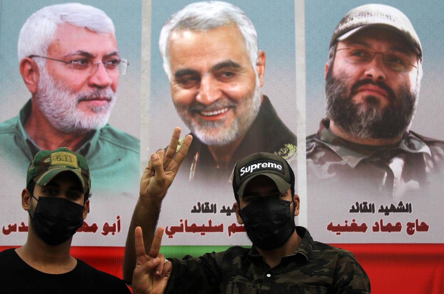 Supporter of the Iran-backed Hashed al-Shaabi (Popular Mobilisation) paramilitary forces pose before a banner showing a montage of (L to R) slain Iraqi paramilitary commander Abu Mahdi al-Muhandis, Iranian commander Qassem Soleimani, and Lebanese Hezbollah commander Imad Mughniyeh during a demonstration outside the entrance to the Iraqi capital Baghdad's highly-fortified Green Zone on November 7, 2020, demanding the departure of remaining US forces from Iraq. Several hundred protesters gathered in the Iraqi capital on Saturday afternoon to demand US troops leave the country in accordance with a parliament vote earlier this year. / AFP / AHMAD AL-RUBAYE