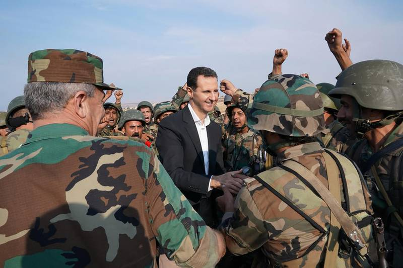 """TOPSHOT - A handout picture released by the official Facebook page for the Syrian Presidency on October 22, 2019, shows Syrian soldiers cheering President Bashar al-Assad during his visit to al-Habit on the southern edges of the Idlib province. Syrian President Bashar al-Assad visited government troops on the front line with jihadists in Idlib, his first visit to the northwestern province since the start of the conflict. - RESTRICTED TO EDITORIAL USE - MANDATORY CREDIT """"AFP PHOTO / Syrian Presidency Facebook page """" - NO MARKETING NO ADVERTISING CAMPAIGNS - DISTRIBUTED AS A SERVICE TO CLIENTS  / AFP / Syrian Presidency Facebook page / - / RESTRICTED TO EDITORIAL USE - MANDATORY CREDIT """"AFP PHOTO / Syrian Presidency Facebook page """" - NO MARKETING NO ADVERTISING CAMPAIGNS - DISTRIBUTED AS A SERVICE TO CLIENTS"""