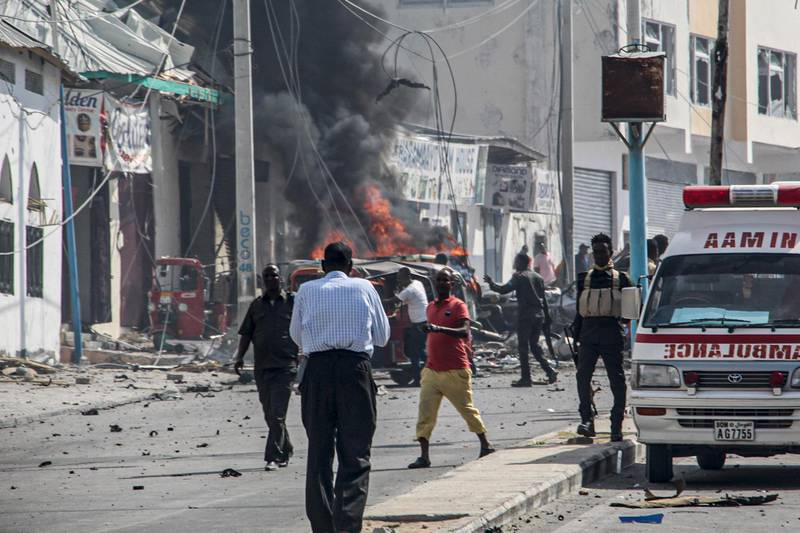 Security officers stand around the site of a car bombing attack near a security checkpoint in Mogadishu, Somalia, on February 13, 2021.  At least three people were killed and eight others wounded after a car bomb detonated near a security checkpoint along a key road in Mogadishu, security official and witnesses said. / AFP / STRINGER