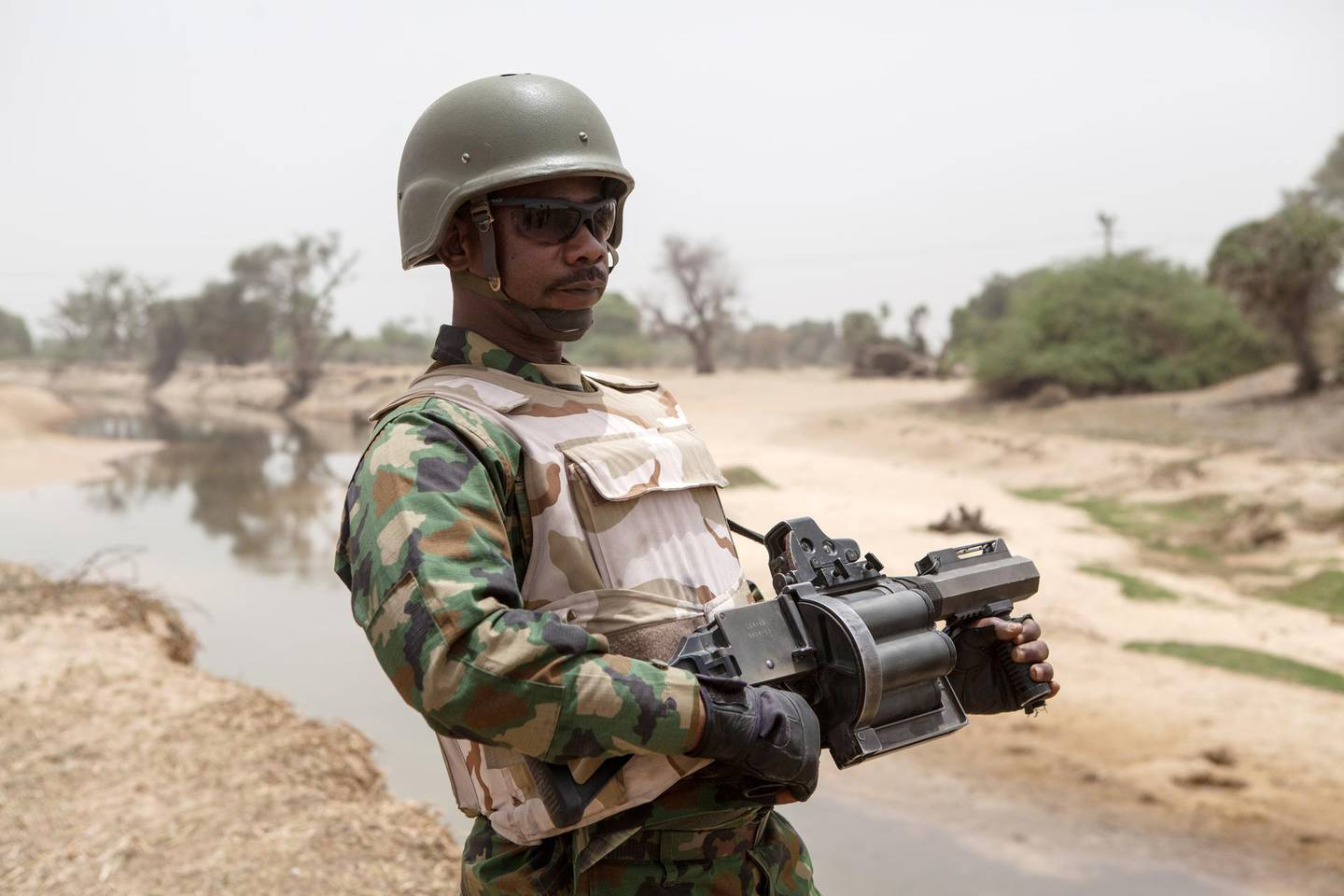 A Nigerian soldier, with a grenade launcher, stands guard near the Yobe river, that separates Nigeria from Niger, on the outskirt of the town of Damasak in North East Nigeria on April, 25 2017 as thousands of Nigerians, who were freed in 2016 by the Nigerian army from Boko Haram insurgents, are returning to their homes in Damasak. - Yagana Bukar's younger brothers Mohammed and Sadiq were among about 300 children kidnapped by Boko Haram from the town of Damasak in remote northeastern Nigeria nearly three years ago. But instead of the global outrage and social media campaign that followed a similar abduction of 219 schoolgirls from the town of Chibok, there were no protests for the children of Damasak. (Photo by Florian PLAUCHEUR / AFP)