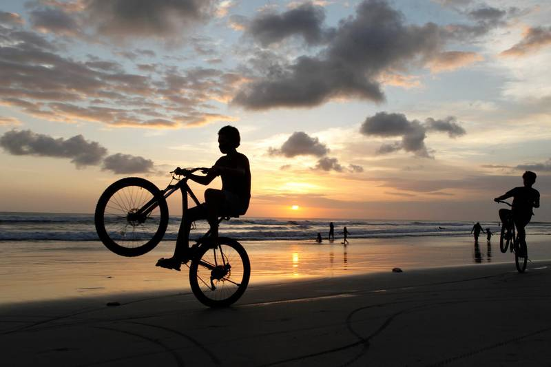 Boys play with their bicycles during sunset on Kuta beach in Bali, Indonesia, Friday, July 10, 2020. Indonesia's resort island of Bali reopened after a three-month virus lockdown Thursday, allowing local people and stranded foreign tourists to resume public activities before foreign arrivals resume in September. (AP Photo/Firdia Lisnawati)