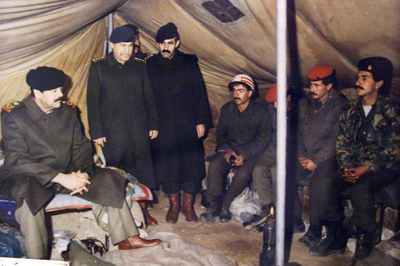 """(FILES) In this photograph made available by the official Iraqi presidential photographer on 26 April 2002, Iraqi President Saddam Hussein (L) is seen sitting in a tent in Najaf (Irak) in 1991 during Gulf War, with unidentified others. Thirty years have passed since Iraqi tyrant Saddam Hussein invaded neighbouring Kuwait, but despite hints of a diplomatic rapprochement, people both countires say the wounds have yet to heal. On August 2, 1990, Saddam sent his military, already exhausted by an eight-year conflict with Iran, into Kuwait to seize what he dubbed """"Iraq's 19th province."""" The two-day operation turned into a seven-month occupation and, for many Iraqis, opened the door to 30 years of devastation which is still ongoing. / AFP / PRESIDENTIAL PALACE / -"""